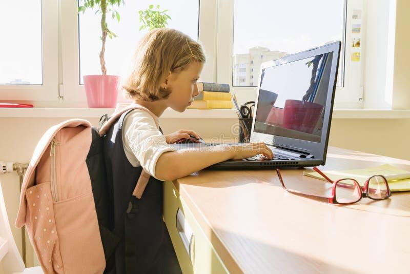 Liten skolflicka som hemma sitter på datoren royaltyfri bild