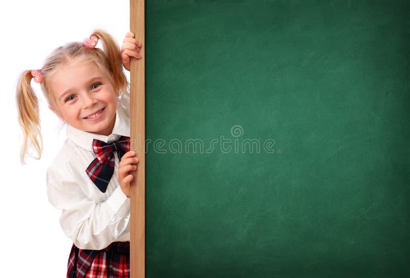Liten skolflicka som kikar bak svart tavla royaltyfri bild