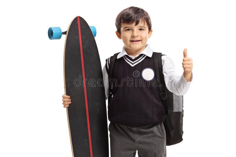 Liten skolpojke med en longboard som gör en tumme upp tecken royaltyfri bild