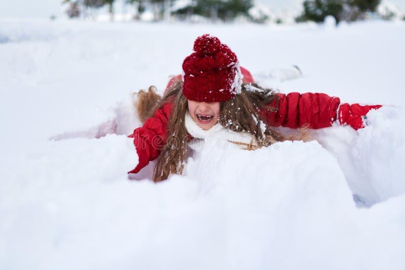 Liten skratta flickarullning i snödriva royaltyfria foton