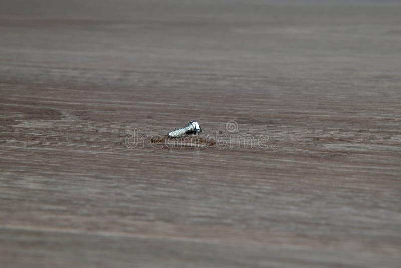 Liten skruv i en droppe av vatten på en träbakgrund fotografering för bildbyråer