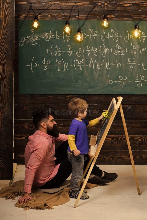Liten snille som lär matematik Lärare- eller faderportionunge som löser likställande på den svart tavlan Skäggig grabb i rosa skj arkivbild