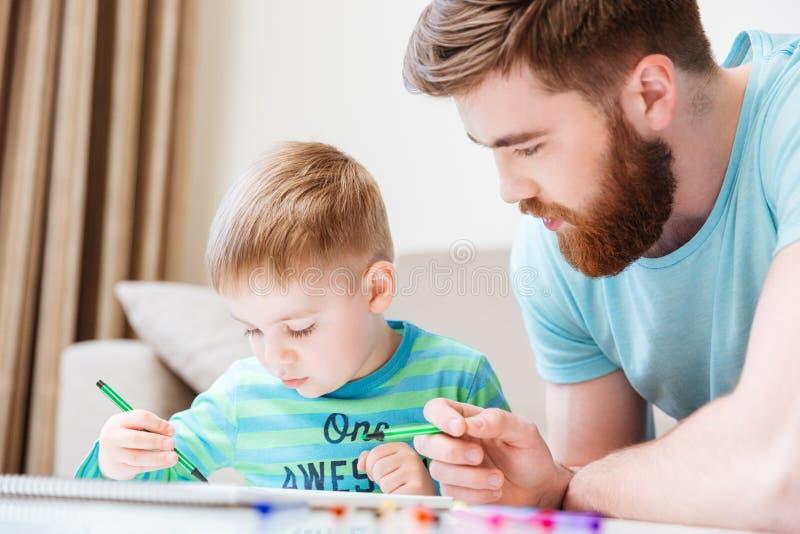 Liten son och hans faderteckning med markörer tillsammans royaltyfria foton