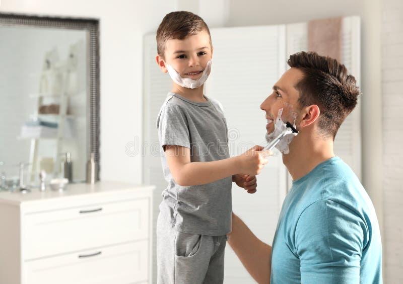 Liten son som rakar hans farsa arkivbild