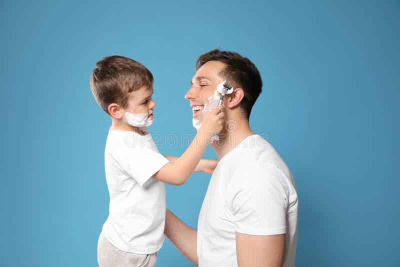Liten son som rakar hans farsa arkivfoton