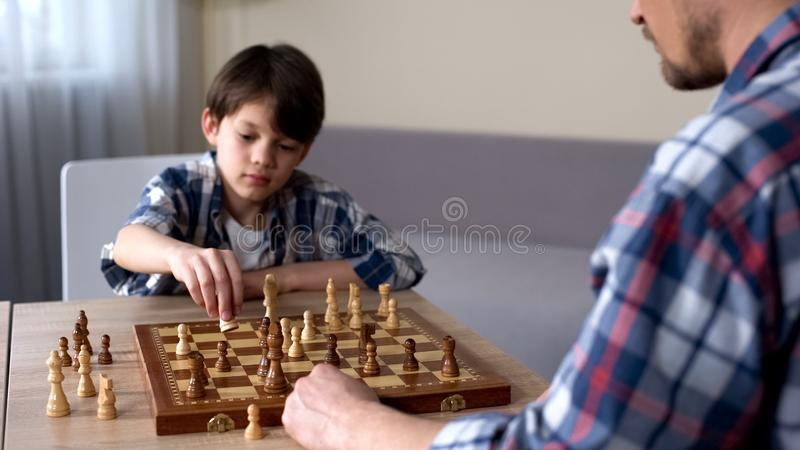 Liten son som spelar schack med fadern hemma, fritidsaktivitet, barndomhobby arkivfoto
