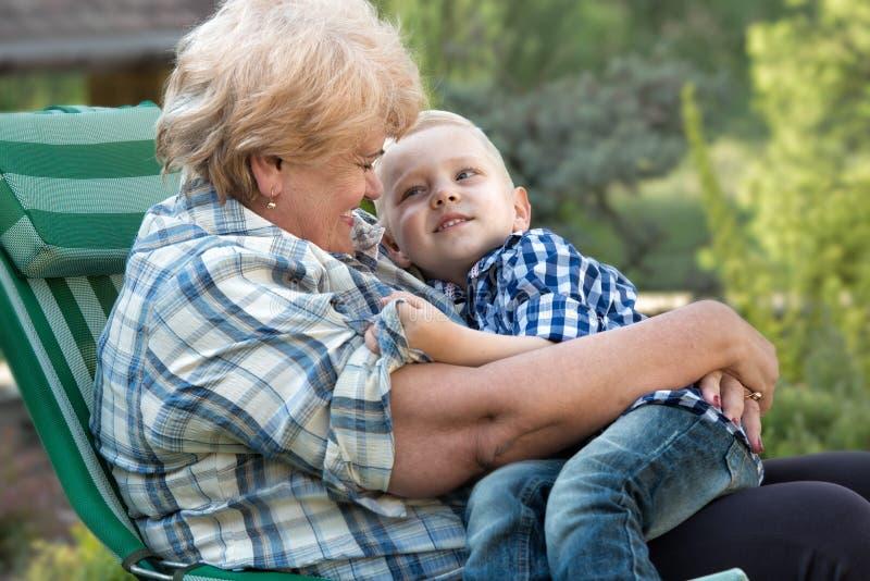Liten sonson som kramar farmodern som sitter i hennes armar Familjferie utomhus royaltyfria foton
