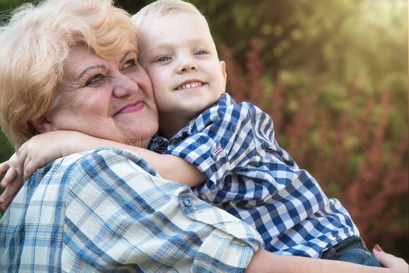 Liten sonson som kramar farmodern som sitter i hennes armar Familjferie utomhus arkivbild