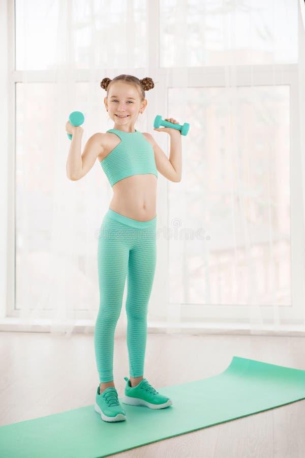 Liten sportig flickagymnast i sportswearen som gör övningar på ett mattt inomhus royaltyfria foton