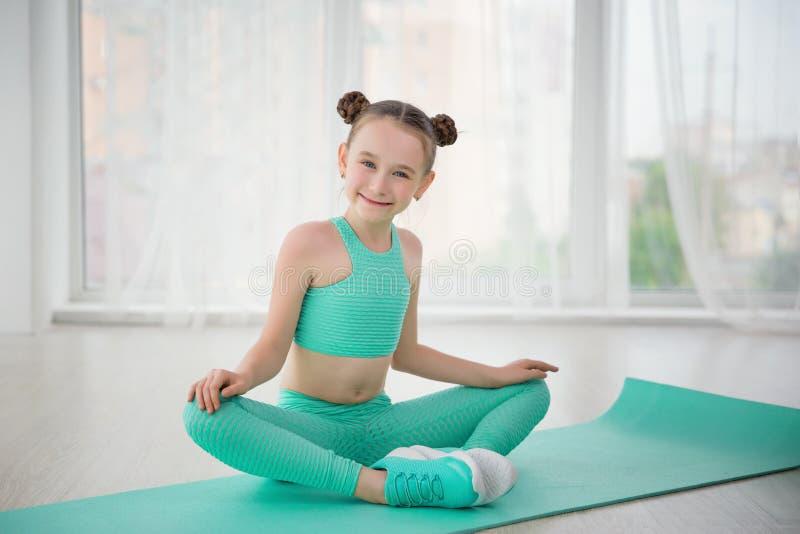 Liten sportig flickagymnast i sportswearen som gör övningar på ett mattt inomhus royaltyfri foto