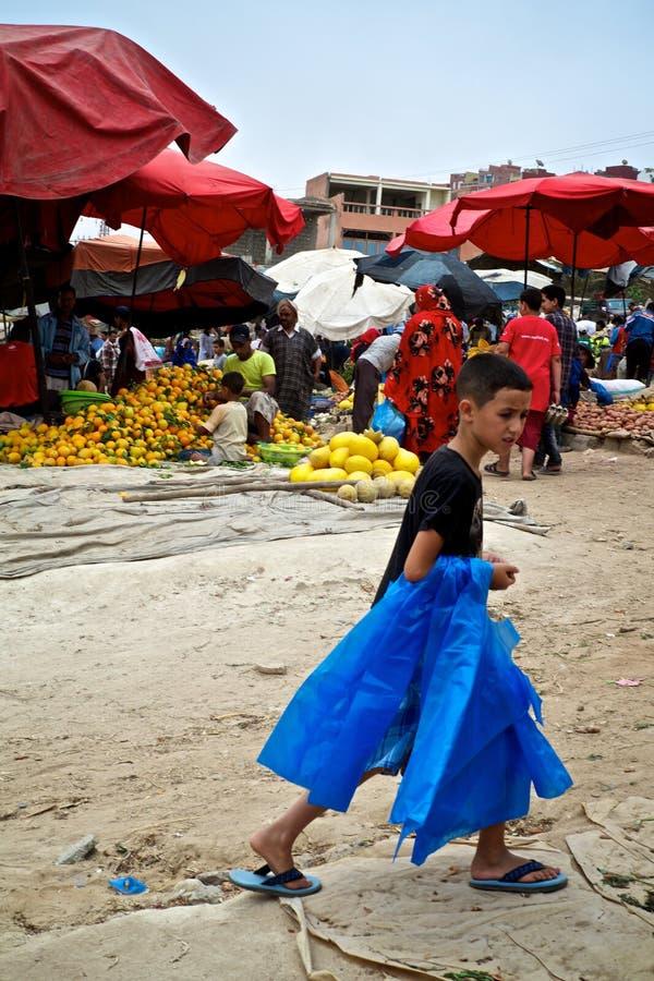 liten stadsöndag marknad för ny jordbruksprodukter med den unga pojken som säljer plastpåsar royaltyfri bild