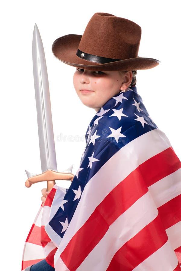 Liten stark flicka i cowboyhatt med amerikanska flaggan och svärdet fotografering för bildbyråer