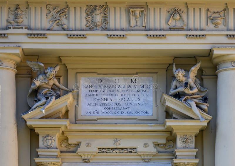 Liten statyer och informationsplatta ovanför den främre ingången till basilikan av St Margaret av Antiochia, Santa Margherita Lig arkivfoton