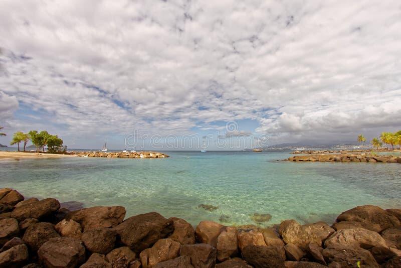 Liten strand på Pointe du Anfall med en sikt på Fort-de-France - Martinique royaltyfri fotografi