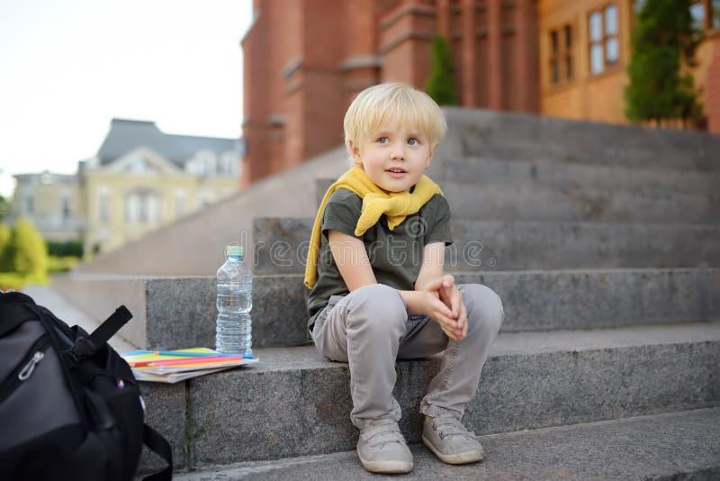 Liten student som sitter på trappuppgång nära skolabyggnaden tillbaka skola till royaltyfria bilder