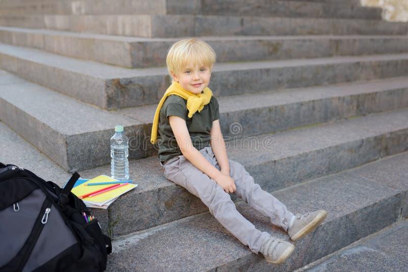 Liten student som sitter p? trappuppg?ng n?ra skolabyggnaden tillbaka skola till arkivfoton