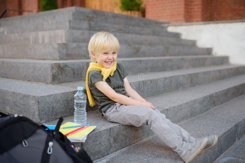 Liten student som sitter p? trappuppg?ng n?ra skolabyggnaden tillbaka skola till arkivbilder