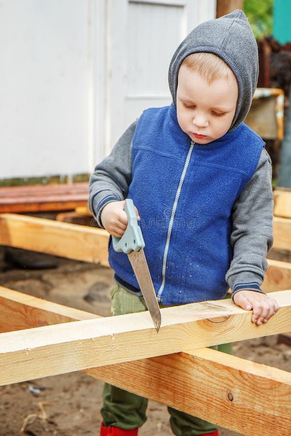 Liten studieintresserad pojke som sågar ett träbräde Hem- konstruktion Li arkivbild