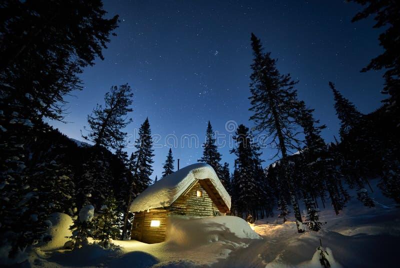 Liten stuga i en härlig snöskog på månenatten royaltyfri bild