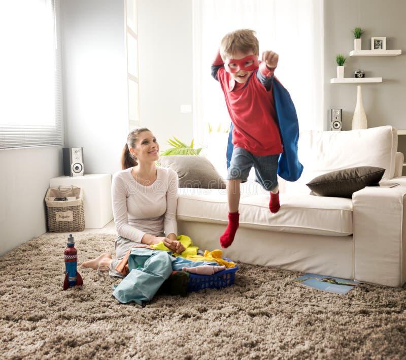 Liten superhero som hjälper hans moder arkivfoton