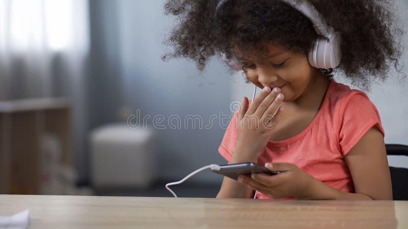 Liten svart flicka som ler, medan surfa internet på smartphonen, föräldra- kontroll royaltyfri foto