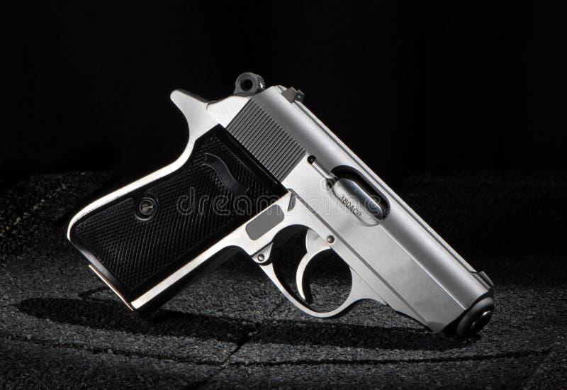 liten svart pistol för bakgrund arkivfoto