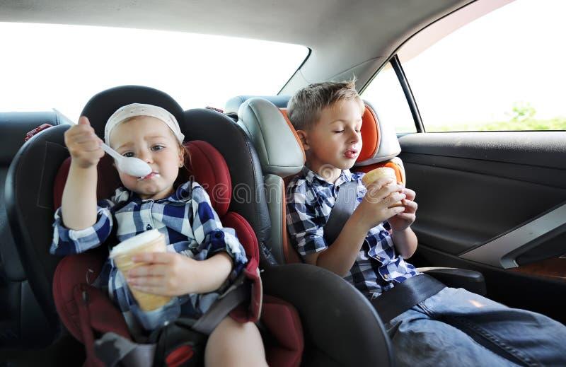 Liten syster och hennes broder i säkerhetsbilsäte som äter söt glass Lilla flickan är nyckfull arkivfoton