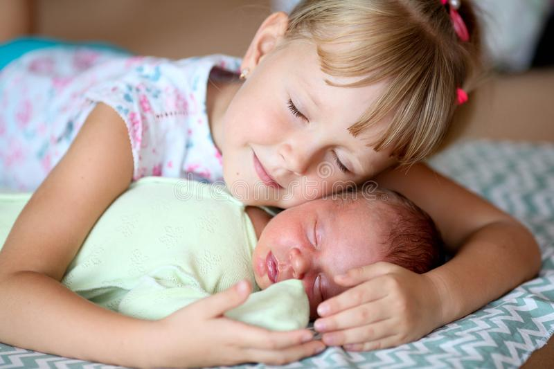Liten syster som kramar hennes nyfödda broder Litet barnunge som möter den nya siblingen  royaltyfria foton
