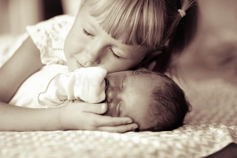 Liten syster som kramar hennes nyfödda broder Litet barnunge som möter den nya siblingen  fotografering för bildbyråer