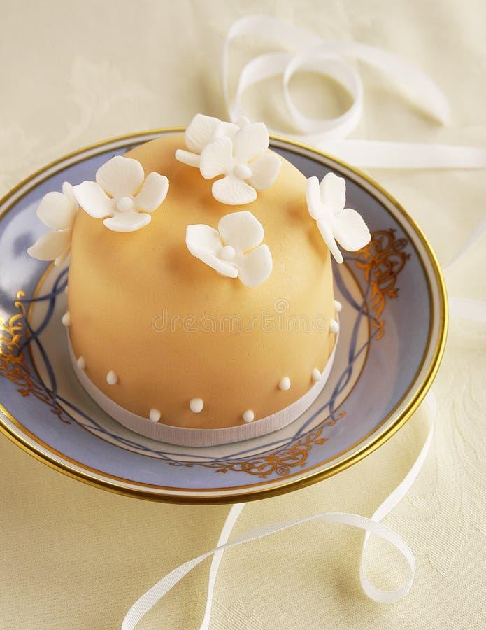 Liten tårta med fondantblommor fotografering för bildbyråer