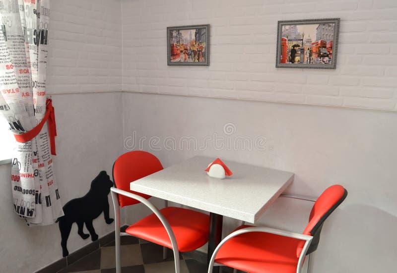 Liten tabell och röda stolar i modernt kafé royaltyfri fotografi
