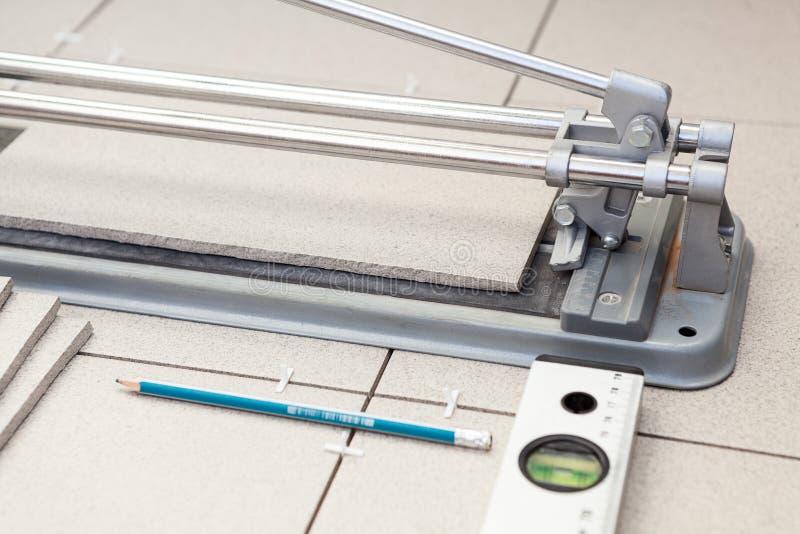 Liten tegelplatta-skärare med att lägga tegelplattor arkivbilder
