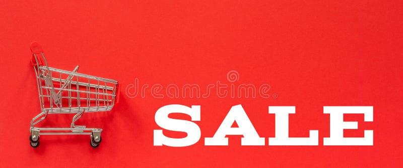 Liten tom shoppa spårvagnvagn och text Sale på röd bakgrund Begreppsförsäljning Kopieringsutrymme för bästa sikt royaltyfri foto