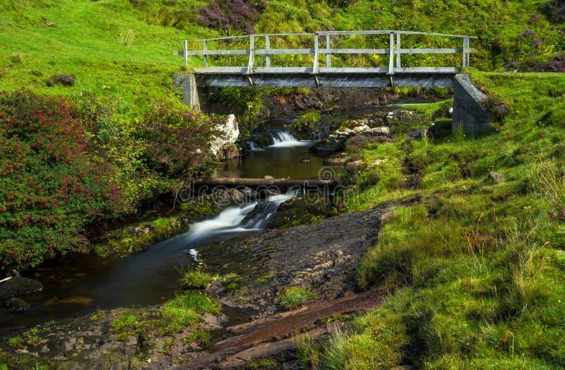Liten träbro över lös liten vik på ön av Skye In Scotland arkivfoton