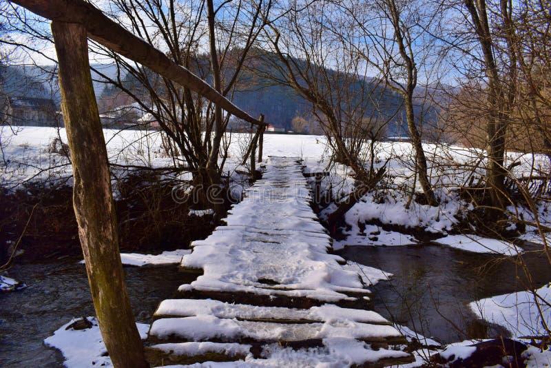 Liten träbro i det insnöat vintern arkivfoton