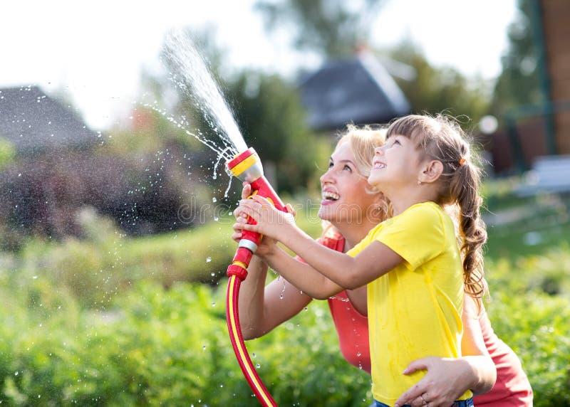 Liten trädgårdsmästareflicka med modern som bevattnar på near hus för gräsmatta fotografering för bildbyråer