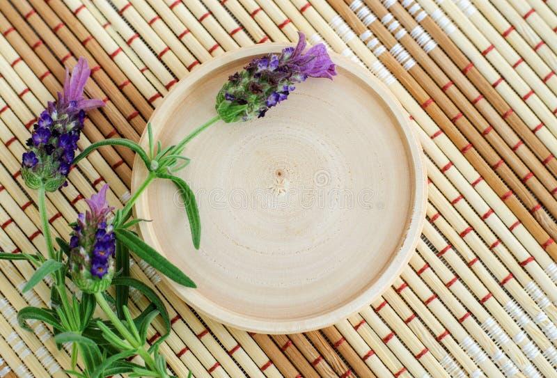 Liten träplatta som ett ställe för text och överträffade lavendelblommor på den matta bakgrunden för bamgoo royaltyfria foton