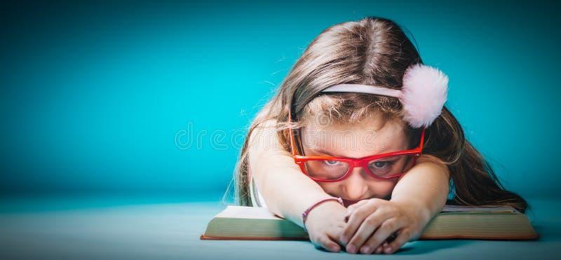 Liten trött flicka som lägger på en öppen bok arkivfoto