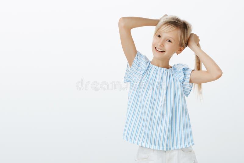Liten trendig flicka som visar henne första örhängen till vännen Stående av det lyckliga skämtsamma europeiska barnet, hållande m royaltyfria bilder
