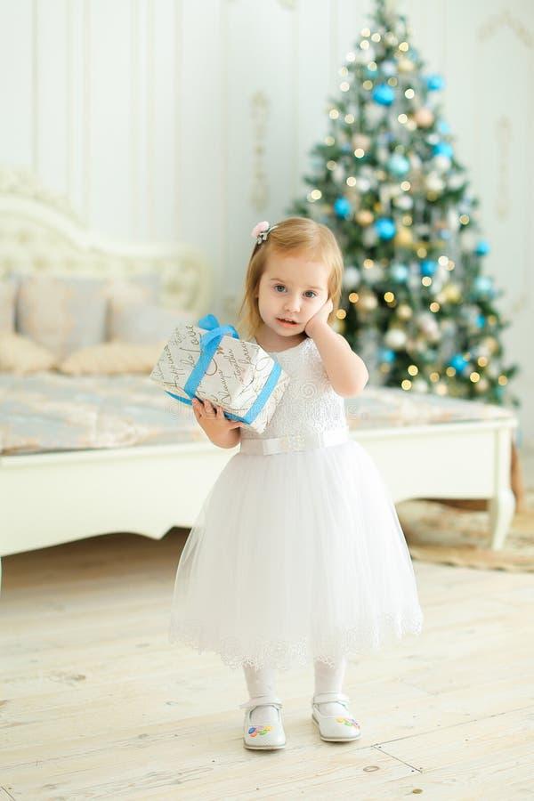 Liten trevlig flicka som håller gåva, den bärande vita klänningen och anseende i sovrum med julgranen royaltyfri bild