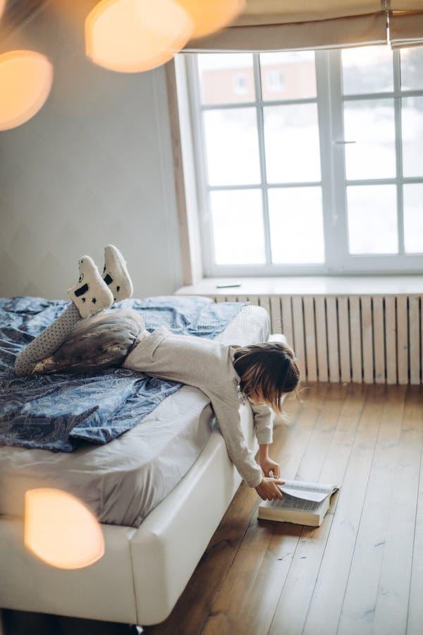 Liten trevlig flicka som rymmer en bok på golvet och vänder dess sidor royaltyfri bild