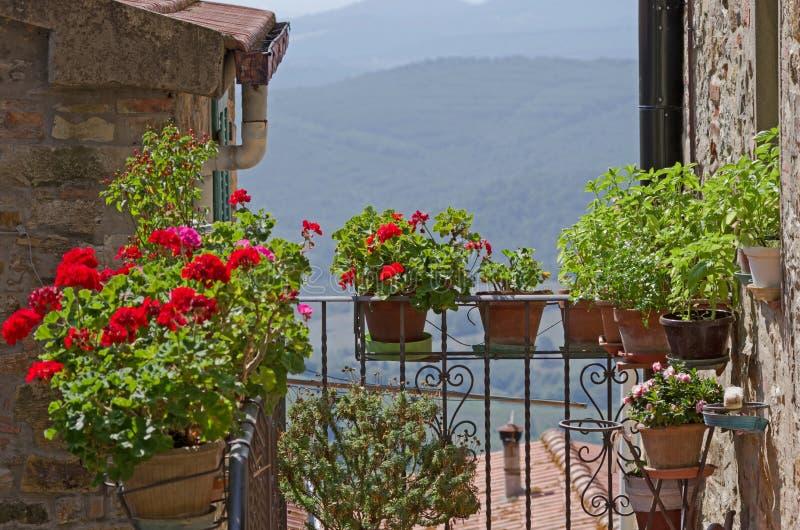 Liten tuscan balkong med blommande pelargon royaltyfri foto