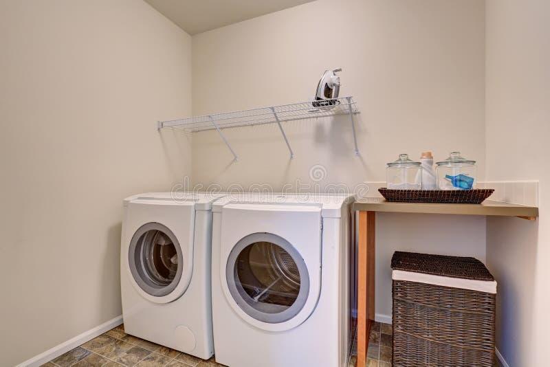 Liten tvättstuga med vita anordningar och den vide- korgen fotografering för bildbyråer