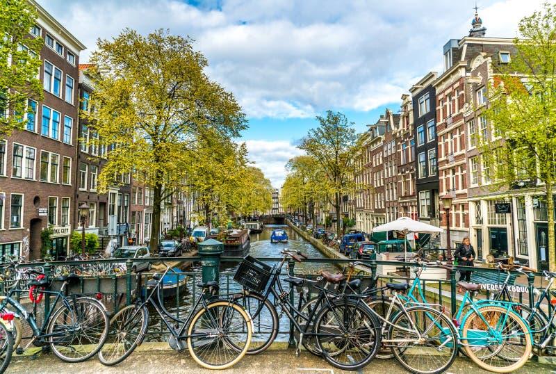 Liten tyst kanal med cyklar på bron framme i mitten av Amsterdam fotografering för bildbyråer