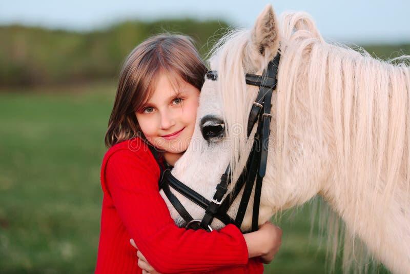 Liten ung flicka i en röd klänning som kramar hans huvud en vit häst royaltyfri foto