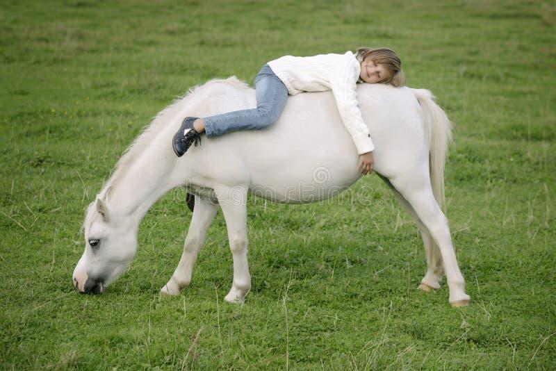 Liten ung flicka i en vit tröja och jeans som tillbaka ligger på baksidan av en vit häst Livsstilstående arkivfoto