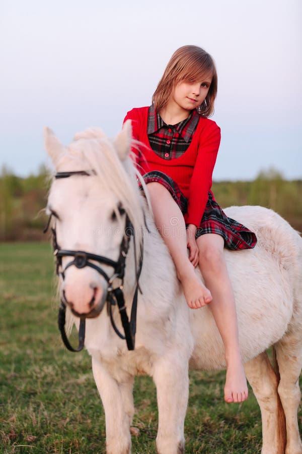 Liten ung flicka som grensle sitter en vit häst och le royaltyfri foto