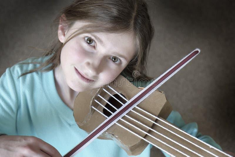 Liten ung flicka som spelar hemlagade Toy Violyn arkivfoton