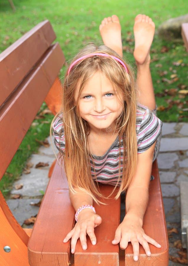 Liten unge - flicka på en bänk royaltyfri fotografi