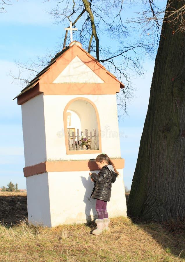Liten unge - flicka som ber vid ett kapell royaltyfri fotografi